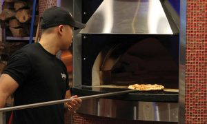 guy putting pizza in wood-fired pizza oven